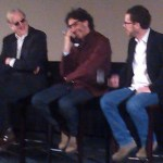 T-Bone Burnett, Joel Coen and Ethan Coen sitting on stage laughing