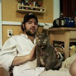 Filmmaker Josh Weissbach sits with his deaf and blind cat, Giblet, on this lap.