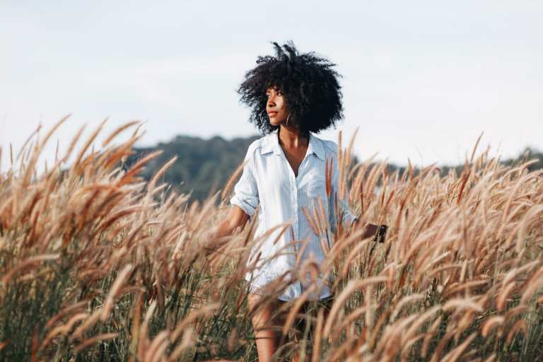 A young African American woman walks through a field at sunset © | Zolotarevs/Shutterstock