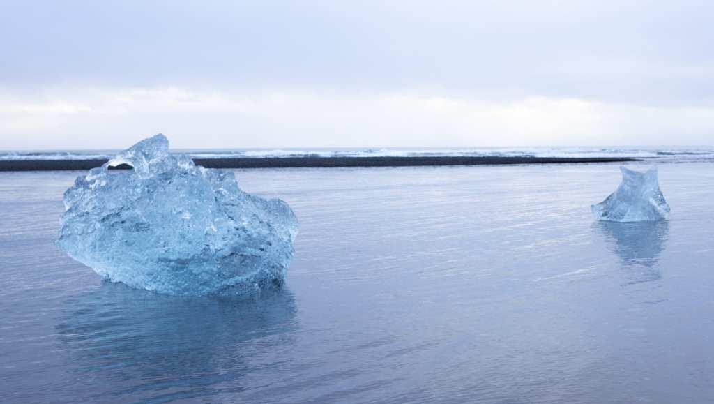Icebergs from the Jökulsárlón lagoon in Iceland, float past the black sand Diamond Beach | © Jeff Cerulli