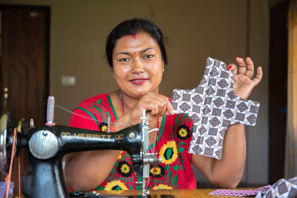 Sangita, 32, holds up a finished reusable sanitary pad | © WaterAid/ Mani Karmacharya