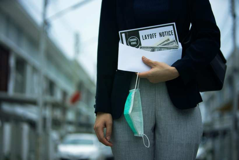 A recently laid off woman holds her severance and lay-off notice | © Shutterstock