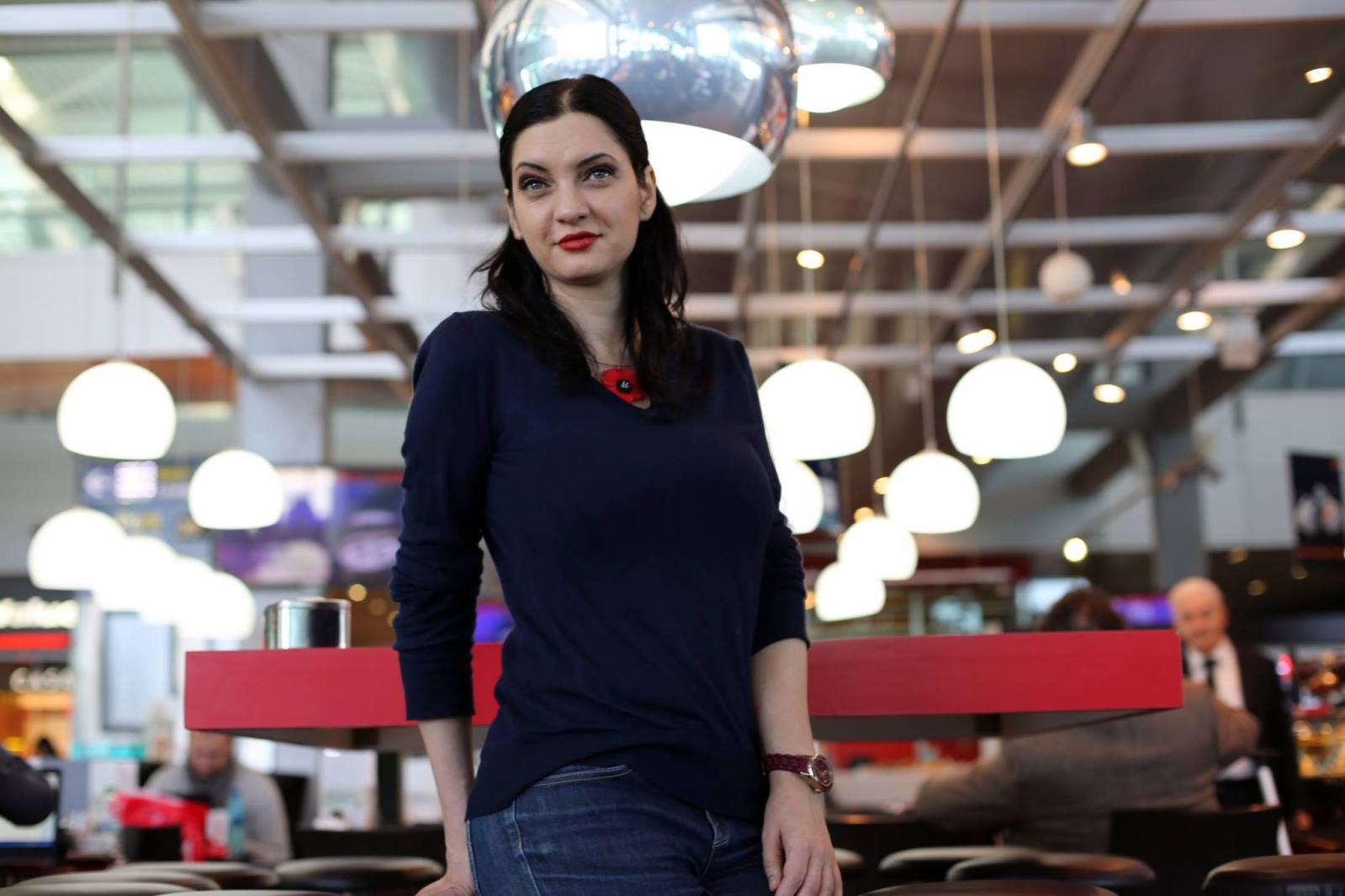 Woman wearing navy blue sweater and red necklace