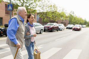 AvD und BVHI machen auf die Bedeutung des Gehörs im Straßenverkehr aufmerksam: Senior überquert mit Hilfe einer Begleiterin einen Zebrastreifen.  Foto: Bundesverband der Hörgeräte-Industrie e.V.  /Fred Froese.