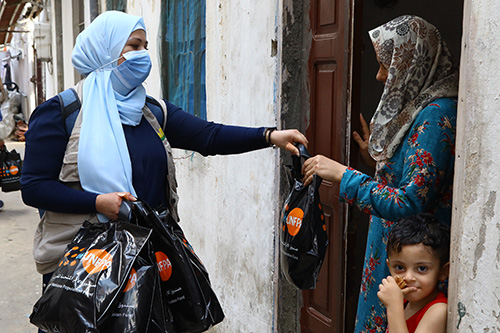 A woman in a blast-affected neighbourhood receives a dignity kit containing hygiene supplies.