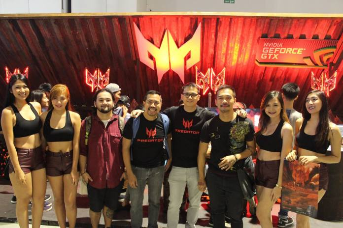 Kjwan poses at the Predator booth with the lovely booth babes!
