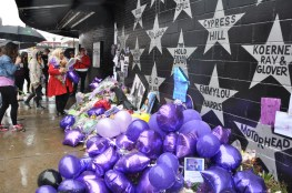 Despite the pouring rain Sunday, people kept coming to leave purple flowers and purple balloons under Prince's First Avenue star.