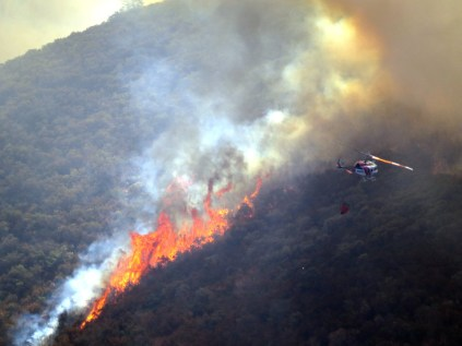CalFire helicopter approaches fire from nearby reservoir Sept. 26 near Moccasin, Calif.
