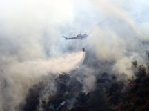 CalFire helicopter drops bucket of water on forest fire near Moccasin, Calif.
