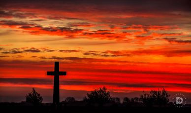 """October 21: """" A Glorious Sunrise."""" I was traveling this morning south of Grand Forks and just when the beautiful clouds, colors and light were coming up for sunrise, I came by this cross. I knew this was meant to be the image I was looking for today."""