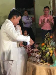 The groom pours a magnum of champagne over a stack of glasses that fills at the next level as the upper level pours over the top.