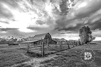 "June 23: ""The Moulton Barns on Mormon Row"": These barns are the most photographed barns in the U.S. With the Teton Mountains in the background, you can see why. Settlers John and Thomas Alma (T.A.) Moulton built these barns on adjacent homesteads. Took an evening image of this Moulton barn with storm clouds above and the sun just peaking through. I liked this one in black and white."
