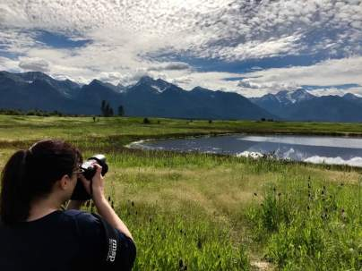 June 20: Kristi Vorland photographing the Mission Mountains north of Missoula. I snapped the pic with my iPhone. Another great day in Montana!