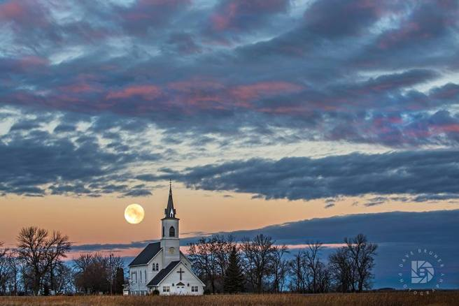 """Nov. 15: Super Moon"" I went out this morning after seeing that the super moon was still very visible when it went between clouds. I used this church in the country for the foreground and waited for the moon to drop into view from the clouds above. The sun was still below the horizon behind me causing the clouds above to get that nice pinkish red glow before sunrise."