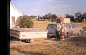 Marian and her children in front of the trusty station wagon pulling the pop-up camper. Slope County Silbernagel farm.