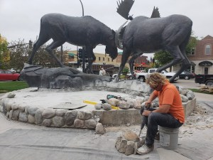 Dennis Riedhammer chisels away mortar from the base of an iconic sculpture of two battling moose outside Cabela's In East Grand Forks, Minn.