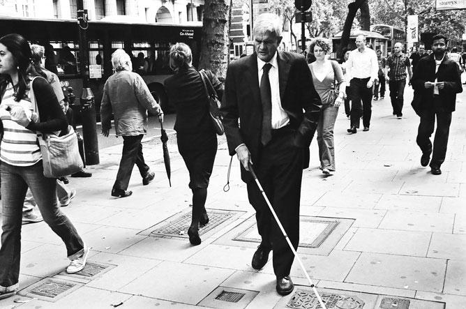 Utcai életkép járókelőkkel s egy öltönyös vak férfival