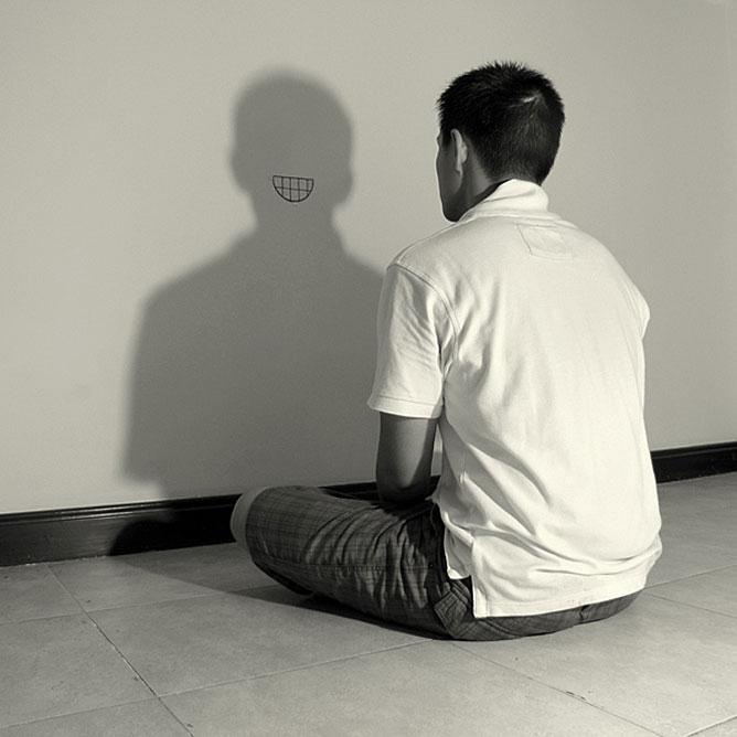 Fallal szemben ülő férfi falon mosolygó árnyékával; zazen.