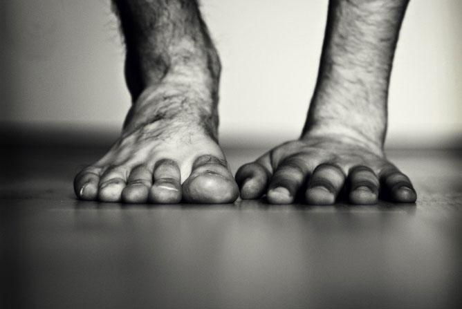 Fekete-fehér kép egy szőrös lábfej és egy tenyér egymás mellett.