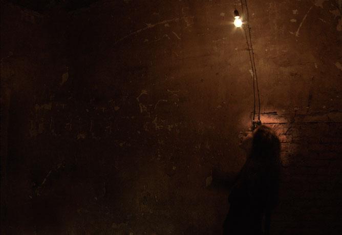 Sötét utcai kép egy fiatal lánnyal aki felnéz a falon lévő fényt keltő izzóra.