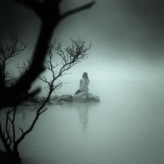 Vízparton magányosan ülő nő.