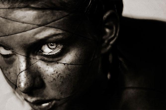 Fekete fehér kép, fémhálóval körbecsavart szeplős női arc, hatalmas szemek.