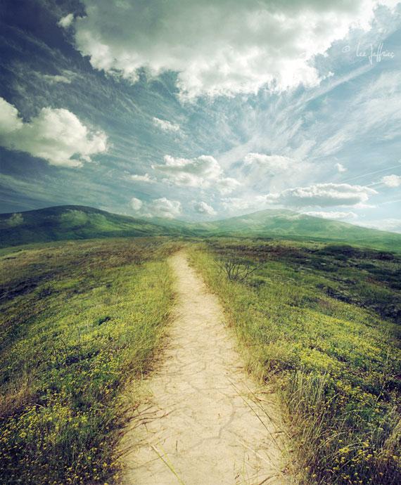 Földes út, hegyekkel a háttérben és felhőkkel az égen