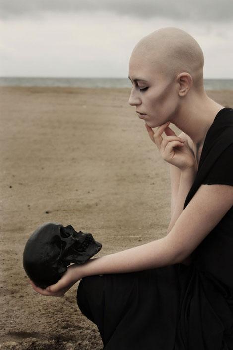 Sivatagi kép egy kopasz lánnyal, aki fekete koponyát tart a kezében.