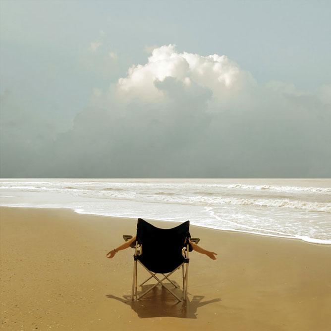 Homokos tengerparti kép kempingszéken ülő szerencsés emberrel.