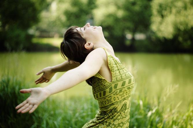 Boldog nő a réten zöld ruhában.