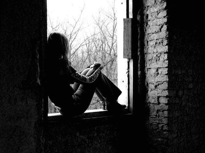 Szomorú lány egy romos épület ablakában.