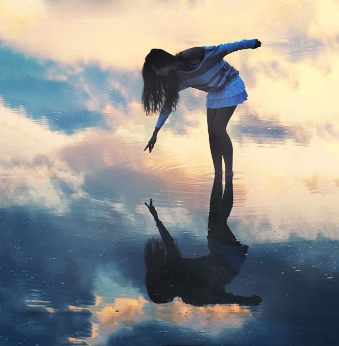 Lány a tóban tükörképével.