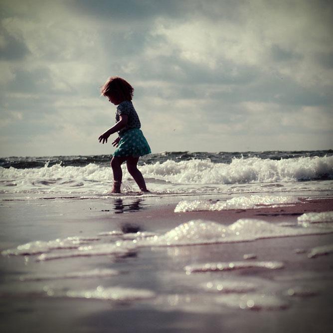 A tengerparton játszó gyermek.
