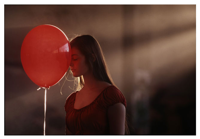 Lány piros lufival.