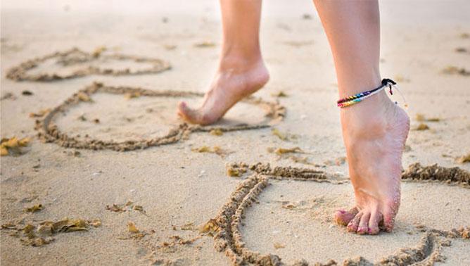 Női lábak a homokban.