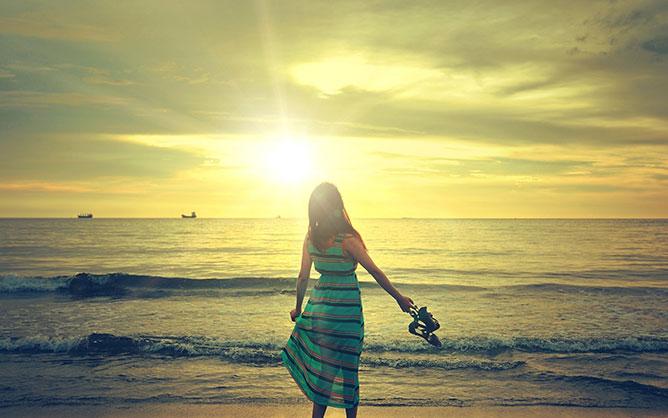 Lány a tengerparti naplementében.