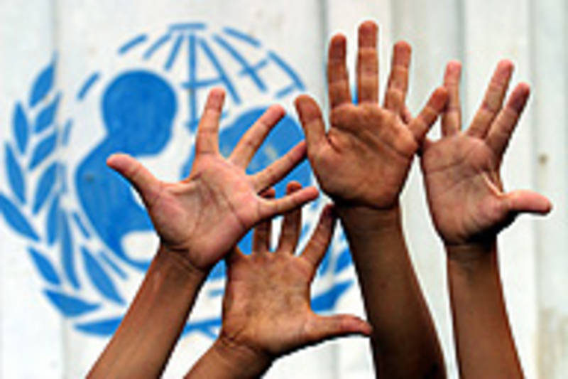 ©UNICEF/HQ04-0604/Giacomo Pirozzi - AZERBAIJAN: Children's hands are raised high in front of a portion of the UNICEF logo painted on the side of a shipping container in the Galagayin settlement for internally displaced persons (IDPs), in the district of Sabirabad, 180 km south of Baku, the capital.