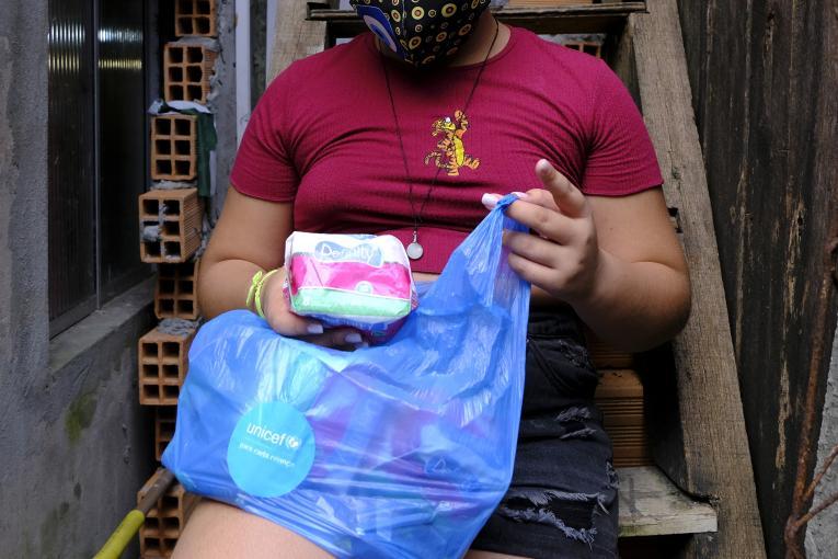 Foto mostra uma adolescente retirando um pacote de absorventes de dentro de uma sacola plástica. Embora o rosto da adolescente não apareça na foto, dá para ver que ela está usando máscara.