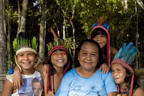 Senhora indígena cercada por quatro crianças também indígenas
