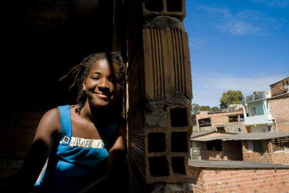 Adolescente está na janela de casa, atrás dela casas de tijolo aparente de uma comunidade de Salvador.
