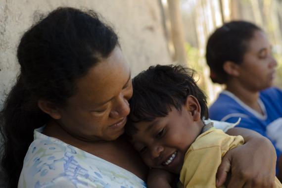 Um menininho indígena está no colo de sua mãe, que o abraça.