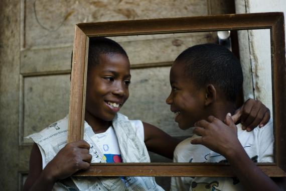 Dois meninos olham um para o outro enquanto sorriem. Há uma moldura vazia na frente deles.