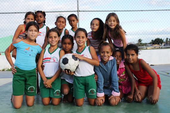 um grupo de meninas está numa quadra de esportes. Algumas estão ajoelhadas na frente de outras. A menina no centro segura uma bola.