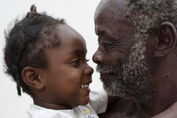 Uma menininha olha para o avô. Ela está sorrindo.