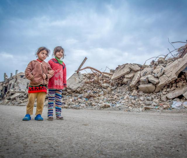 Two Young Girls Standing Amidst Rubble