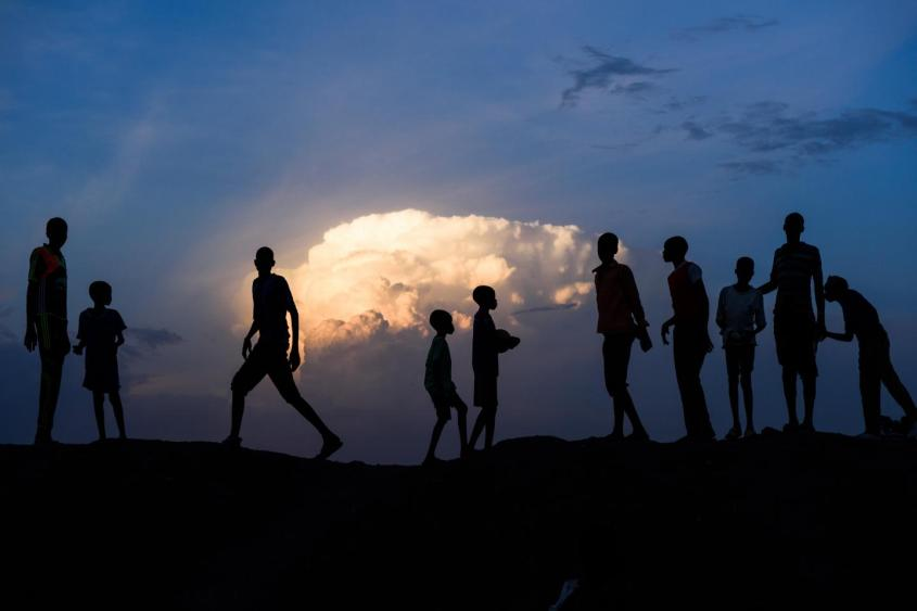 Silhouettes of children in front of a sunset, South Sudan