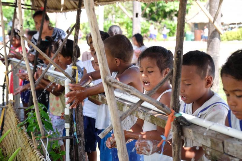 Young children in Kiribati wash their hands outside in 2019.