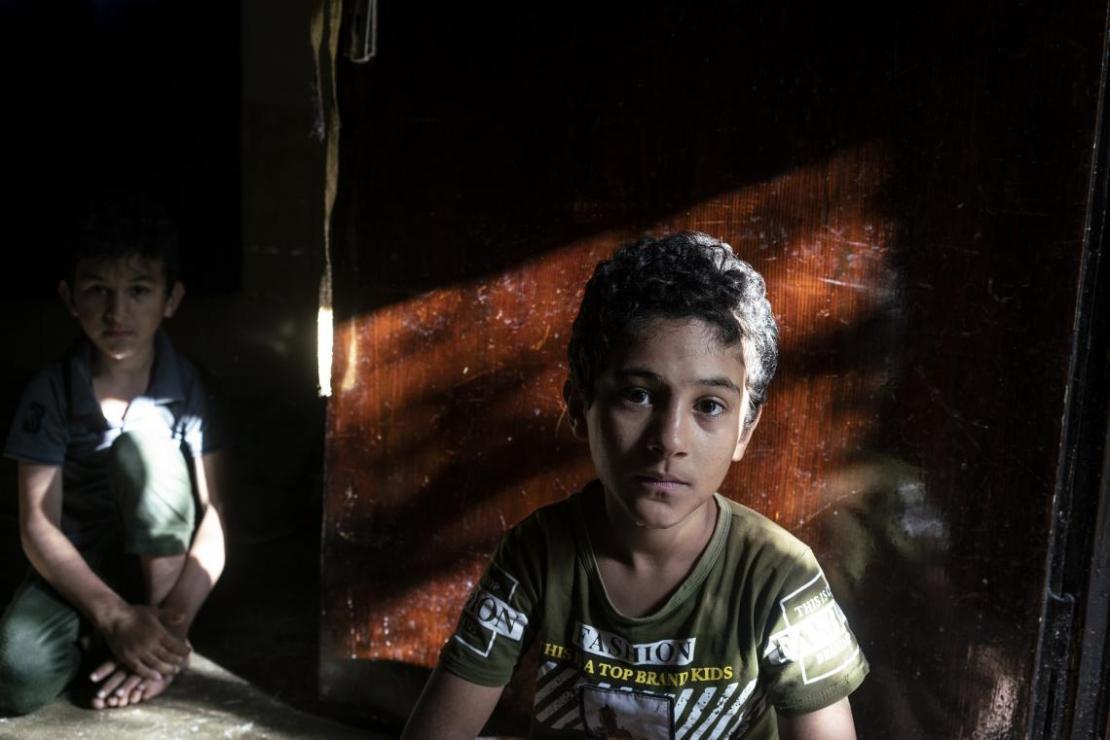 Dos refugiados sirios sentados en el suelo de un refugio en Jordania.