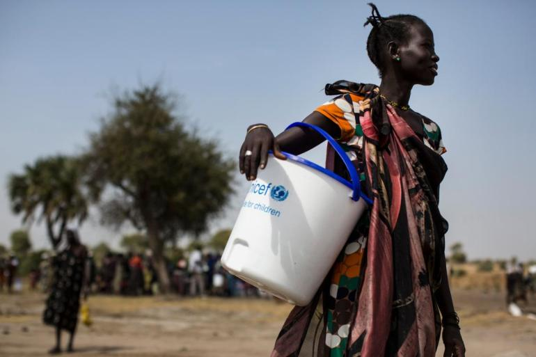 Une femme porte un seau fourni par l'UNICEF