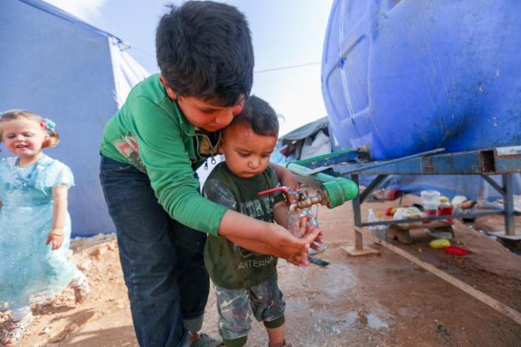 Children wash hands in the Maarat Misrin camp north of Idlib, Syrian Arab Republic